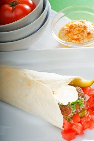 traditional falafel wrap on pita bread with fresh chopped tomatoes photo