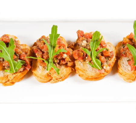 fresh tipycal italian bruschetta with tomato and arugula on top photo