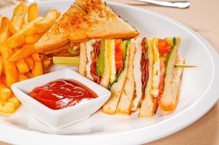 fresh triple decker club sandwich with french fries on side photo