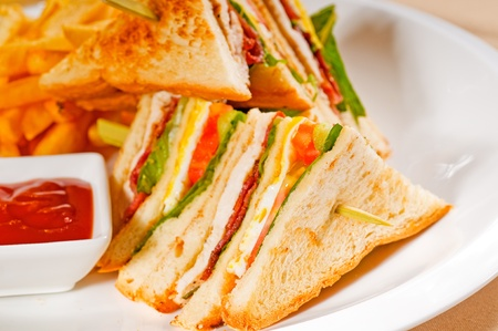 fresh triple decker club sandwich with french fries on side