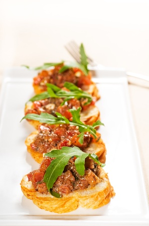fresh tipycal italian bruschetta with tomato and arugula on top 스톡 사진