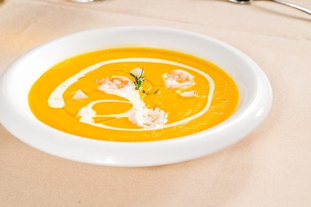 fresh pumpkin and shrimps cream soup ,with milk cream on top photo