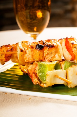 fresh chicken and vegetables skewers on a palm leaf thai style photo