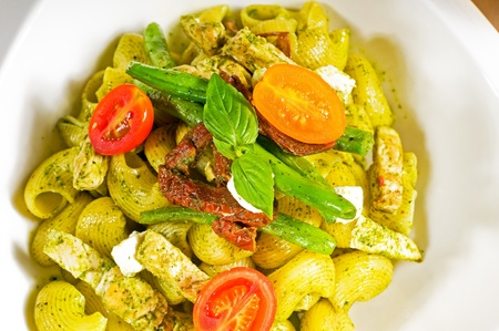 fresh lumaconi pasta and pesto sauce with vegetables and sundried tomatoes,tipycal italian food photo