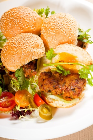 four fresh and delicious mini chicken burgers on a plate ,close up photo