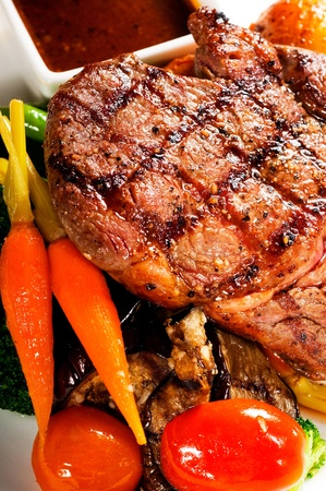 fresh grilled ribeye steak with broccoli,carrot and cherry tomatoes on side photo