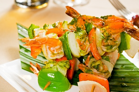 fresh and colorfull grilled shrimps and vegetables skewers on a palm leaf ,thai style photo