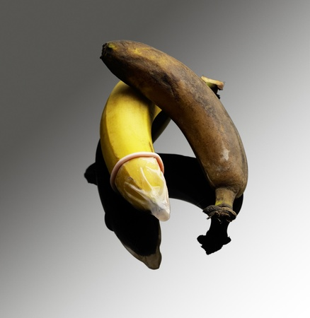 two bananas one good with condom one rotten without condom safe sex concept Stock Photo