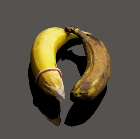 two bananas one good with condom one rotten without condom safe sex concept Stock Photo - 9742708