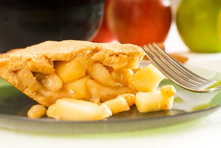 apple tart: fresh homemade apple pie over green glass dish macro colseup eating  with fork