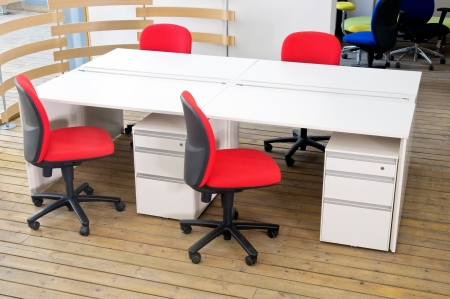 office desks ,and red chairs cubicle set view from top over wood flooring  photo