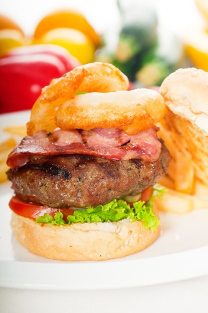 classic american hamburger sandwich with onion rings and french fries,with fresh vegetables on background, MORE DELICIOUS FOOD ON PORTFOLIO photo