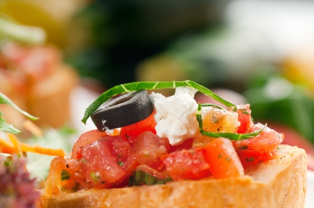 original Italian fresh bruschetta,typical finger food, with fresh salad and vegetables on background,MORE DELICIOUS FOOD ON PORTFOLIO Stock Photo - 10323000