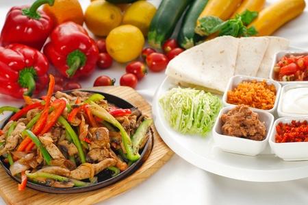 plato de comida: fumar original fajita hirviente caliente servido en chapa de hierro y verduras frescas sobre fondo, m�s DELICIOUS alimentos en cartera