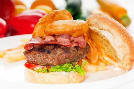 classic american hamburger sandwich with onion rings and french fries,with fresh vegetables on background photo