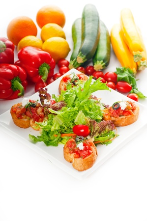 original Italian fresh bruschetta,typical finger food, with fresh salad and vegetables on background