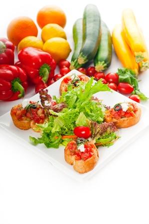 Original italienischen frisch Bruschetta, typische Fingerfood, mit frischen Salaten und Gemüse auf Hintergrund