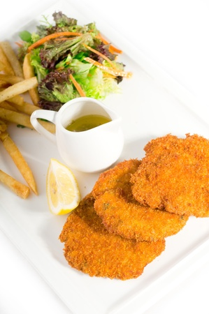 classic breaded Milanese veal cutlets with french fries and vegetables on background