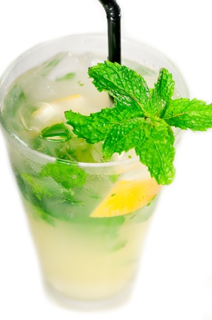 mojito caipirina cocktail with fresh mint leaves ,yerba-buena, with lime and black straw isolated on white background photo