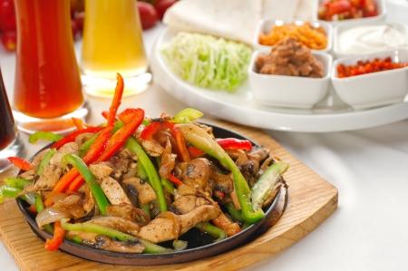 Original Fajita sizzling Rauchen heiß serviert auf eisernen Teller, mit Auswahl an Bier und frisches Gemüse auf Hintergrund, mehr DELICIOUS FOOD ON PORTFOLIO Standard-Bild