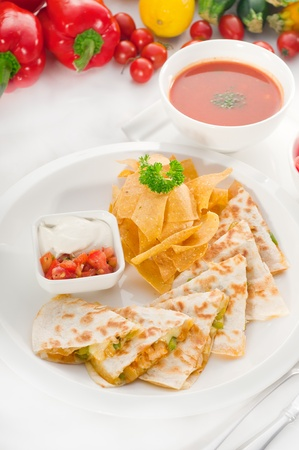 original Mexican quesadilla de pollo with nachos  served with gazpacho soup and watermelon ,with fresh vegetables on background. Stock Photo
