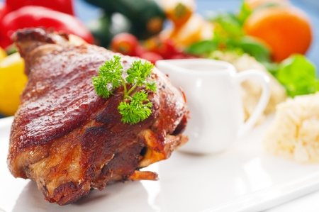 original German BBQ pork  knuckle served with mashed potatoes and  sauerkraut ,fresh vegetables on background,MORE DELICIOUS FOOD ON PORTFOLIO