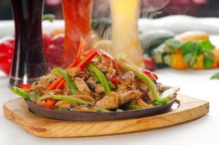 Original Fajita sizzling Akt serviert auf Eisenplatte, mit Auswahl an Bier und frisches Gemüse auf den Hintergrund, auf mehr köstliche FOOD ON PORTFOLIO