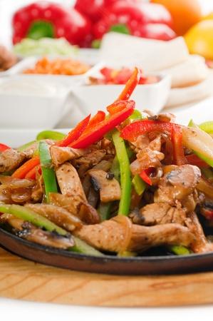Original Fajita sizzling Rauchen heiß serviert auf eisernen Teller und frisches Gemüse auf Hintergrund, mehr DELICIOUS FOOD ON PORTFOLIO Lizenzfreie Bilder