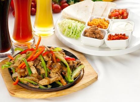 원래 fajita 지글 지글 흡연 뜨거운 맥주와 배경에 신선한 야채의 선택과, 봉사 철 접시에, 더 맛있는 음식에 포트폴리오