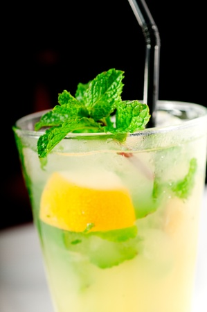 mojito caipirina cocktail with fresh mint leaves ,yerba-buena, with lime and black straw