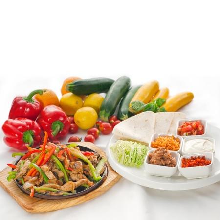 Original fajita sizzling Akt serviert auf heißer Platte und frisches Gemüse auf den Hintergrund.