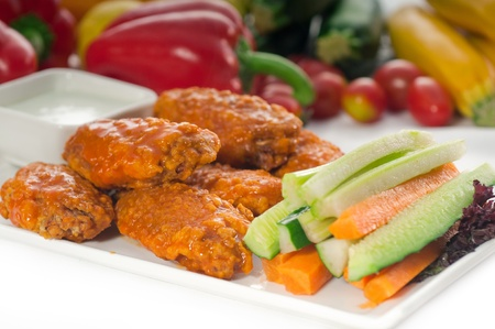 classic  buffalo chicken wings served with fresh pinzimonio and vegetables on background. photo