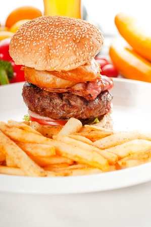 classic american hamburger sandwich with onion rings and french fries,glass of  beer and fresh vegetables on background  photo