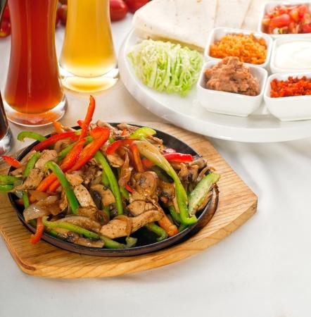 Original fajita sizzling Akt serviert auf Eisenplatte, mit Auswahl an Bier und frisches Gemüse auf den Hintergrund