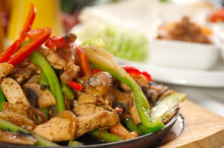 original fajita sizzling smoking hot served on iron plate and fresh vegetables on background