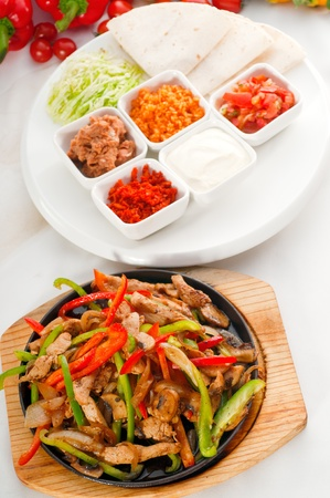 original plate: original fajita sizzling smoking hot served on iron plate and fresh vegetables on background