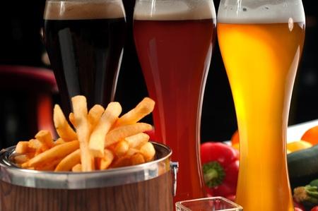 frische Pommes frites auf einem Holz Eimer mit Auswahl an Bieren und frisches Gemüse auf Hintergrund