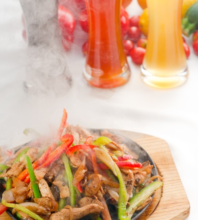 original fajita sizzling smoking hot served on iron plate ,with selection of beer and fresh vegetables on background ,MORE DELICIOUS FOOD ON PORTFOLIO Stock Photo - 11052490