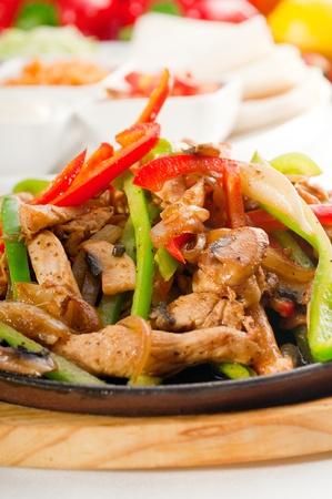 Original fajita sizzling Akt serviert auf heißer Platte und frischem Gemüse auf Hintergrund, mehr Leckeres Essen auf Portfolio- Standard-Bild