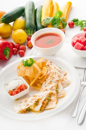 original Mexican quesadilla de pollo with nachos  served with gazpacho soup and watermelon ,with fresh vegetables on background,MORE DELICIOUS FOOD ON PORTFOLIO photo