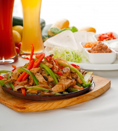 Original fajita sizzling Akt serviert auf heißer Platte, mit einer Auswahl an Bier und frischem Gemüse auf Hintergrund, mehr Leckeres Essen auf Portfolio-