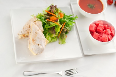 sliced watermelon: tuna fish and cheese sandwich with fresh mixed salad ,watermelon and gazpacho soup on side,with fresh vegetables on background ,MORE DELICIOUS FOOD ON PORTFOLIO