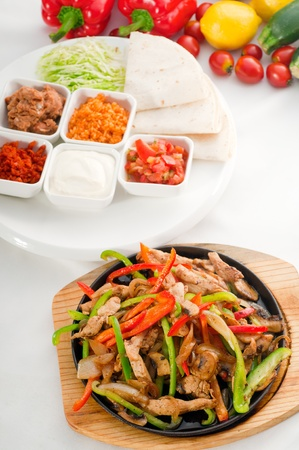original fajita sizzling smoking hot served on iron plate and fresh vegetables on background ,MORE DELICIOUS FOOD ON PORTFOLIO Stock Photo - 11263302