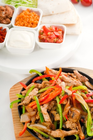sizzling: original fajita sizzling smoking hot served on iron plate and fresh vegetables on background.