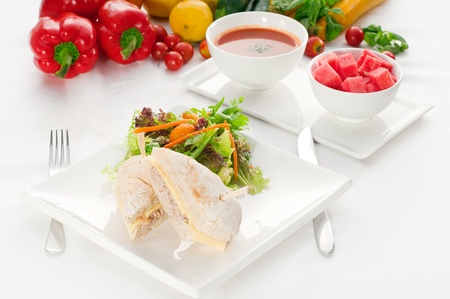 tuna fish and cheese sandwich with fresh mixed salad ,watermelon and gazpacho soup on side,with fresh vegetables on background . photo