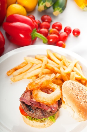 classic american hamburger sandwich with onion rings and french fries,with fresh vegetables on background. photo