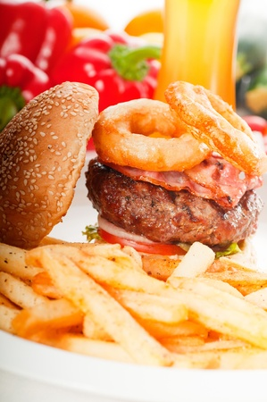 classic american hamburger sandwich with onion rings and french fries,glass of  beer and fresh vegetables on background. photo
