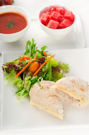 tuna fish and cheese sandwich with fresh mixed salad ,watermelon and gazpacho soup on side,with fresh vegetables on background. photo