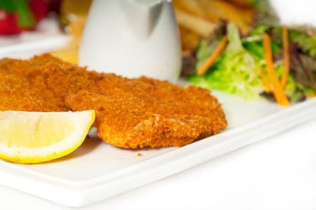 classic breaded Milanese veal cutlets with french fries and vegetables on background ,MORE DELICIOUS FOOD ON PORTFOLIO photo