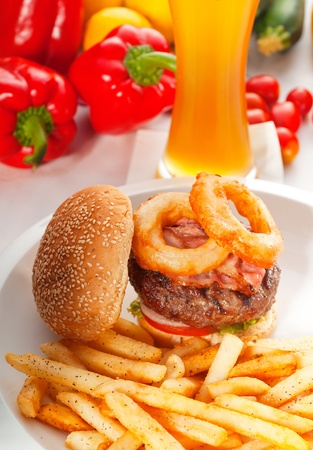 classic american hamburger sandwich with onion rings and french fries,glass of  beer and fresh vegetables on background,  MORE DELICIOUS FOOD ON PORTFOLIO photo